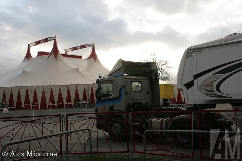 Scania 114 Kerst wordt in Duitsland groots gevierd. We kennen allemaal de kerstmarkten, maar ook het kerstcircus is een belangrijk onderdeel van de Duitse cultuur in de periode rond de jaarwisseling. Ik ben gek op circussen, vooral vanwege het bijzondere wagenpark wat ze vaak hebben. Bij het kerstcircus in Heilbronn viel dat een beetje tegen, totdat ik ineens een wel heel bekende truck zag staan. Hij stond dan misschien bij een Duits circus, en staat op Portugees kenteken, maar de Scania P114 die tegenwoordig een woonwagen trekt, zag ik vroeger toch zeker een paar keer per week. Het is een oude truck van Hoogland BV uit Ferwert! De truck uit 1998 is in juni 2012 geëxporteerd, daarna kwam hij dus schijnbaar bij een circusartiest terecht. Hoe dan ook, erg leuk om onverwacht weer oog in oog met deze truck te staan, jeugdsentiment! Helaas stond hij achter een hek en de man in beeld was te druk aan het bellen om aanspreekbaar te zijn teneinde toestemming te vragen.